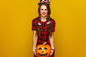 happy woman on yellow background holding jack-o-lantern pumpkin
