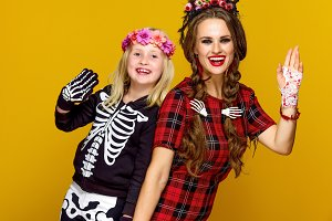 smiling modern mother and child in halloween costume handwaving