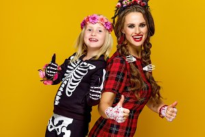 mother and child in halloween costume showing thumbs up