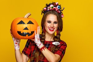 smiling young woman showing jack-o-lantern pumpkin