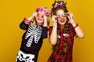 mother and daughter in halloween costume having fun time