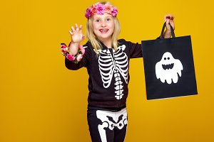 girl on yellow showing shopping halloween bag and frightening