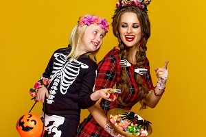 mother and child stealing halloween candies isolated on yellow