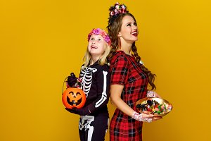 mother and daughter with Halloween candies looking at copy space