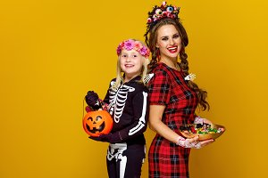 smiling modern mother and daughter with Halloween candies