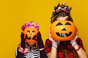 mother and child holding jack-o-lantern pumpkins in front of faces