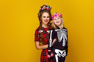mother and child in halloween costume on yellow background
