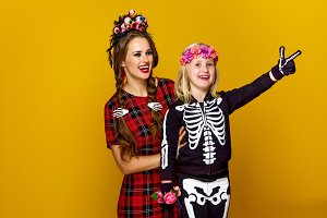 mother and daughter in halloween costume pointing at something