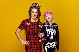mother and daughter in halloween costume isolated on yellow