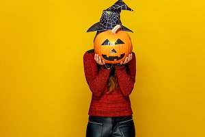 woman holding sad jack-o-lantern pumpkin in front of face
