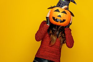 young woman holding jack-o-lantern pumpkin in front of face