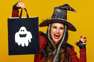 smiling modern woman showing shopping bag and frightening