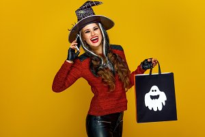 woman with Halloween shopping bag speaking on a mobile phone