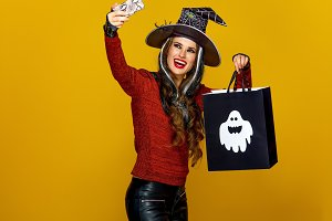 woman with Halloween shopping bag taking selfie with cellphone