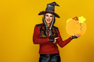 smiling woman isolated on yellow background pointing at pumpkin