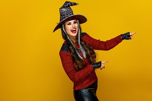 smiling woman in halloween witch costume pointing at something