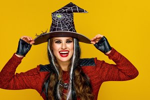 smiling woman in halloween costume isolated on yellow background