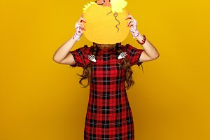 woman on yellow background holding pumpkin in front of face