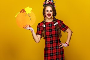 happy woman in halloween costume showing pumpkin
