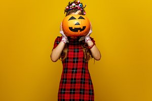 woman with halloween pumpkin in front of face isolated on yellow