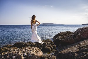 Bride standing on rocks on a sea shore and looking at water