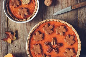 Pumpkin pies on old wooden table