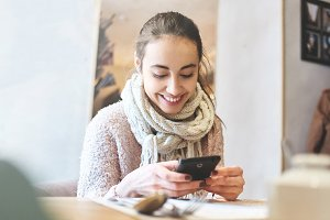 woman in cafe using smartphone