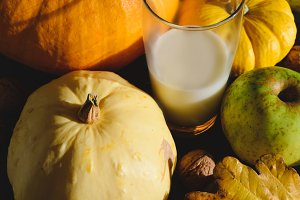pumpkins apples nuts and glass of milk on table autumn still life