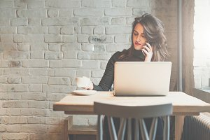 Front view of young businesswoman sitting at table in coffee shop and talking on cell phone while drinking coffee and using laptop. In background white brick wall. Freelancer working outside office.