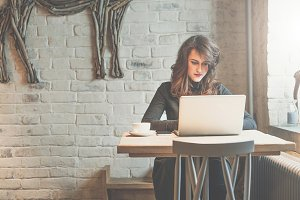 Front view of young businesswoman sitting at table in coffee shop and using laptop,near cup of coffee. In background white brick wall.Freelancer working outside office. Girl online shopping, blogging.