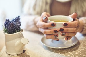 womans hands with cup of tea