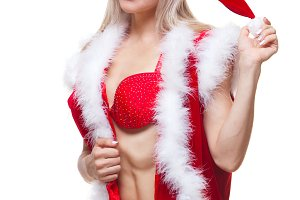 Christmas. Sport, activity. Muscular beautiful sexy girl wearing santa claus clothes isolated on white
