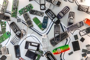 Many disassembled cellular phones against white background