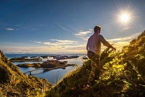 Hiker going to the top of mount Festvagtinden on Lofoten islands