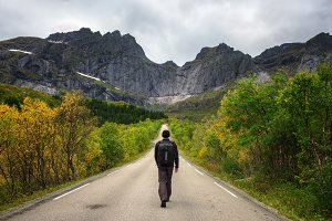 Hiker walks on a scenic road on Lofoten islands in Norway