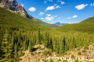 Tourists walking towards the Moraine Lake in canadian Rocky Mountains