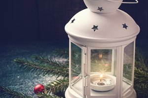 Burning Candle Lantern and Christmas composition of spruce branches and balls