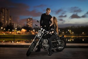 A guy, a girl and a motorcycle. The side of the road, the lights of the night city