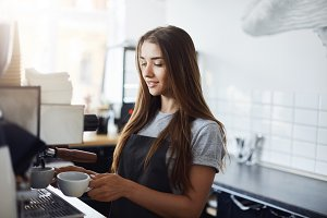 Young female barista preparing coffee in the morning. Running a successful business requires dedication.