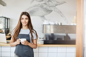 Portrait of young woman running a cafe and pastry shop standing near coffee machine looking at camera holding a cup of cappucino.