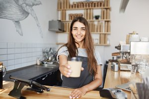 Young female barista handing a cup of cappucino or late to customer looking at camera smiling. Brewing fresh coffee for great taste.