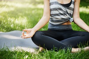 Cropped shot of young female meditating in a public park or behind her house outdoors away from technology.
