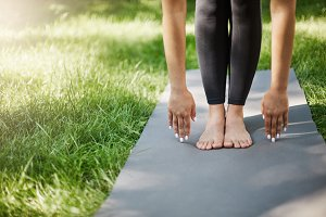 Cropped shot of woman doing pilates or yoga or exercises in park. Hands and feet planted on yoga mat.