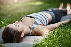 Close up of young female meditating and relaxing on a yoga mat on grass in a city park on a sunny summer day.