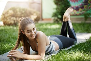 Portrait of fit female fitness trainer laying on yoga mat on a grass outdoors. Healthy body concept.