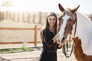Portrait of young girl standing next to a horse looking at camera smiling.