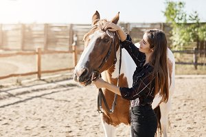 Beautiful female farm manager taking care and petting a horse.