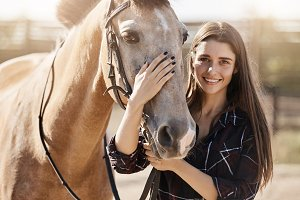 Portrait of beautiful woman petting a horse on animal farm or ranch dreaming to become a forage supplier.