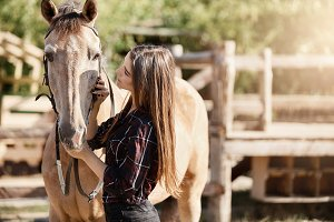 Young woman talking to her horse on a ranch. Good career opportunity working outdoors with animals.