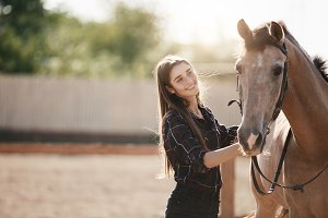 Young female farm owner taking care about a horse on an animal ranch on a summer day.